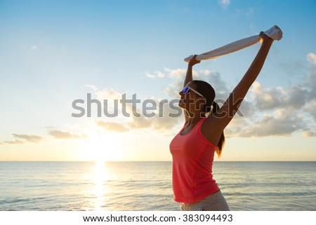 Fitness happy woman celebrating fitness workout success towards the sea and sunset at the beach. Training motivation and healthy lifestyle concept. - stock photo
