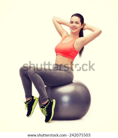 fitness, healcare and dieting concept - smiling teenage girl doing exercise on fitness ball - stock photo