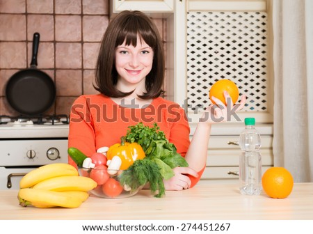 Fitness, healthcare and diet concept - smiling woman with fruits vegetables and bottle of water in the kitchen, pointing at healthy food. - stock photo