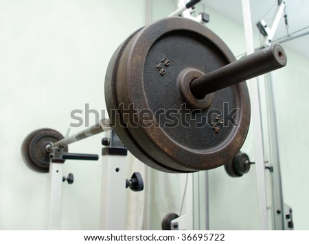fitness heavy barbell in white holder in gym club - stock photo