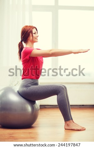 fitness, home and diet concept - smiling redhead girl exercising with fitness ball at home - stock photo