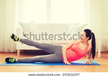 fitness, home and diet concept - smiling teenage girl doing exercise for legs on floor at home - stock photo