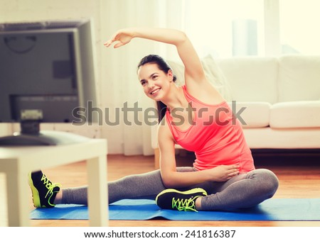fitness, home and diet concept - smiling teenage girl streching on floor and watching tv at home - stock photo