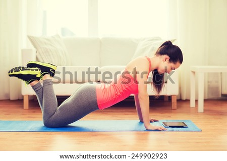 fitness, home, technology and diet concept - smiling teenage girl doing push-ups and looking at tablet pc computer at home - stock photo