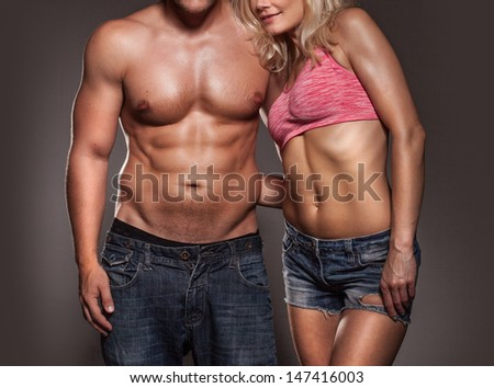 Fitness image of a man and woman's torso isolated on black - stock photo