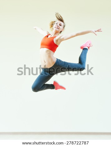 fitness instructor jumping during aerobics dancing exercises in sport club - stock photo