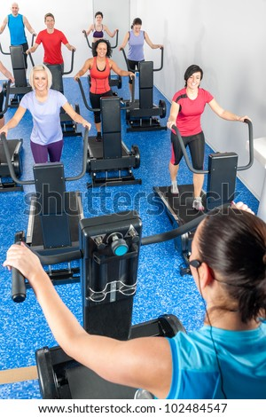 Fitness instructor leading treadmill running class at health club - stock photo