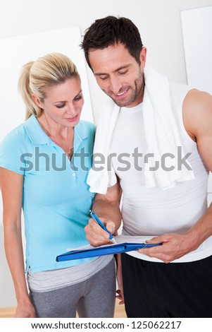 Fitness instructor taking notes after a workout with an attractive athletic young woman standing alongside - stock photo