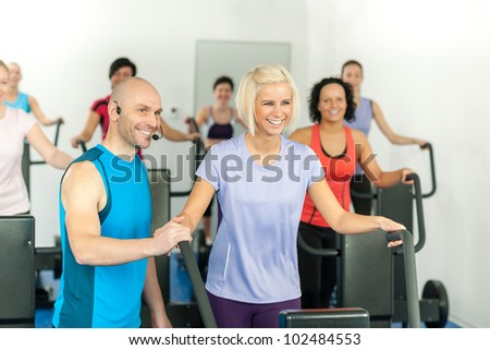 Fitness instructor with gym people exercise on cross-trainer - stock photo