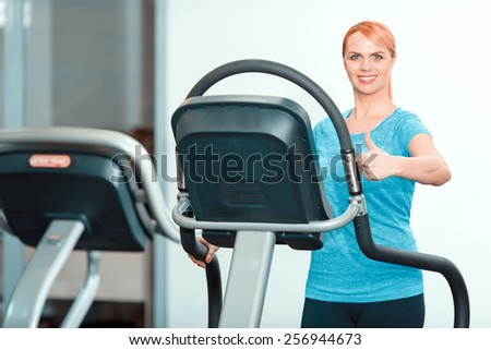 Fitness is my life. Portrait of beautiful mature woman in sports clothing having a workout on a treadmill and showing her thumb up in the gym - stock photo