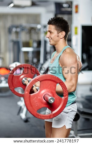 Fitness man doing biceps workout with barbell in a gym - stock photo