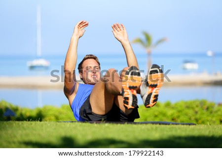 Fitness man doing sit-ups exercise for abs outdoors. Fit male athlete cross training jackknife sit up during workout. Muscular handsome young caucasian man working out outside. - stock photo