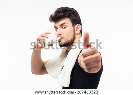Fitness man drinking milk and showing thumb up isolated on a white background - stock photo