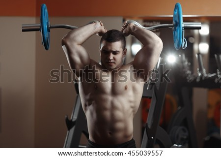 Fitness man exercising with barbell in gym. Fitness man deadlift barbell in the gym. Fitness man in the gym. Sports and fitness - concept of healthy lifestyle. - stock photo