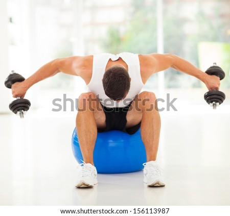 fitness man exercising with dumbbells sitting on gym ball - stock photo