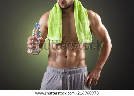 Fitness man holding a bottle of fresh water on black background - stock photo