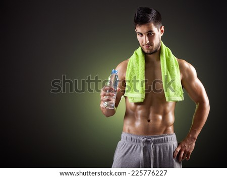 Fitness man holding a bottle of fresh water on dark background - stock photo