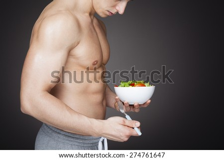 Fitness man holding a bowl of fresh salad on grey background - stock photo