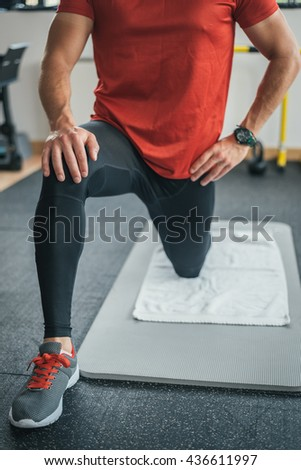 Fitness man stretching legs before gym workout. Sporty male athlete on floor mat and towel warming up. - stock photo