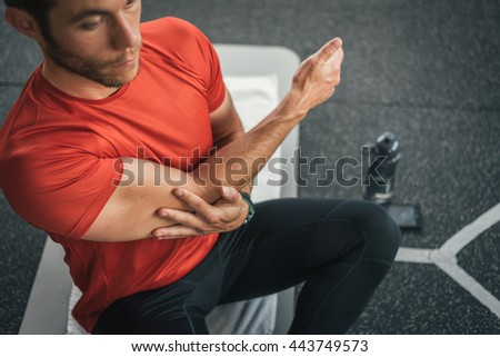 Fitness man stretching shoulder for warming up before gym indoor workout. Male athlete exercising arm before working out. - stock photo