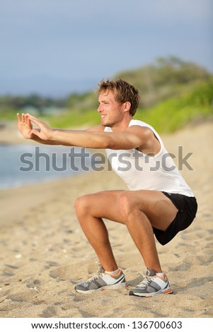 Fitness man training air squat exercise on beach outside. Fit male exercising crossfit outside. Young handsome caucasian male fitness model and instructor outdoors - stock photo
