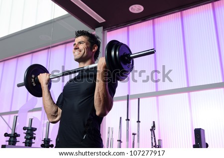 Fitness man training biceps in gym. Male athlete lifting weights. - stock photo