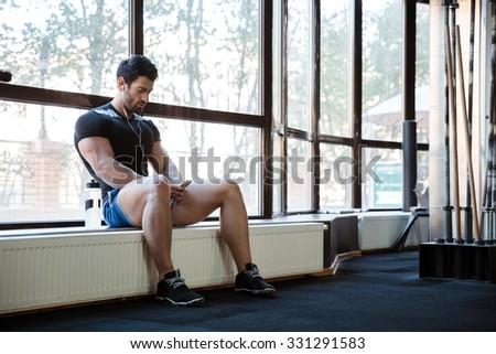 Fitness man wearing blue shorts and black t-shirt listening to music sitting on windowcill - stock photo