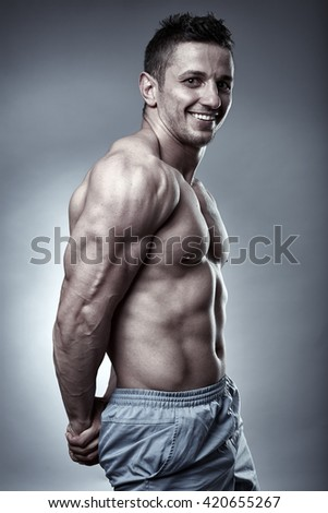 Fitness model displaying his physique over gray background, studio shot - stock photo