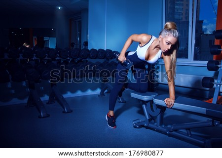 Fitness model doing exercises with dumbbell in gym - stock photo