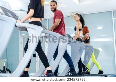 Fitness Motion in life. Sports people running on the treadmill at the gym. Athletes wearing sportswear and running in the gym a rear view athletes. - stock photo