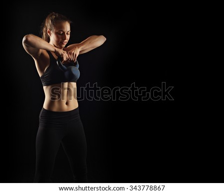 Fitness on black, kettlebell workout - stock photo