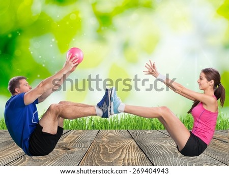 Fitness. One caucasian couple man woman personal trainer coach exercising tossing fitness ball silhouette studio isolated on white background - stock photo