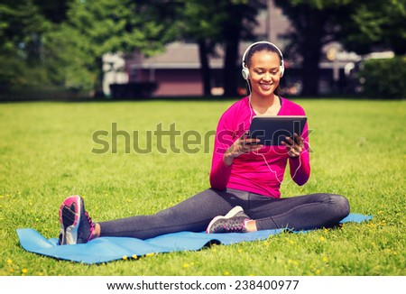 fitness, park, technology and sport concept - smiling african american woman with tablet pc computer and headphones on mat outdoors - stock photo