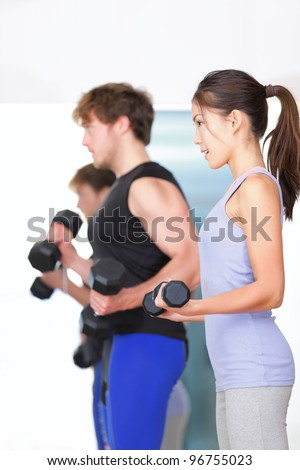 Fitness people in gym. Couple strength training lifting weights during indoor fitness workout. Woman lifting dumbbells training biceps in focus. - stock photo