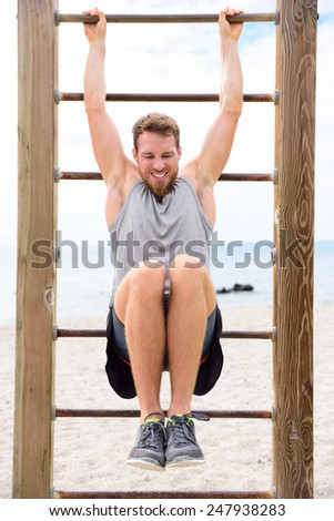 Fitness people - man training abs by lifting legs on cross fit bar rack outside on outdoor gym station. - stock photo