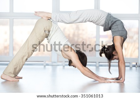 Fitness practice, group of two beautiful fit young people working out in sports club, doing stretching workout together in class, downward facing dog pose with bridge exercise, full length - stock photo