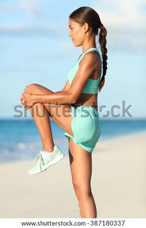 Fitness runner woman doing warm-up routine on beach before running, stretching leg muscles with standing single knee to chest stretch. Female athlete preparing legs for cardio workout in sportswear. - stock photo