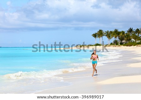 Fitness runner woman running on tropical white sand beach nature landscape outdoors. Beautiful nature in Caribbeans with person jogging living a healthy lifestyle for weight loss in summer. - stock photo