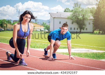 Fitness running couple jogging on athletics stadium track open air during hot summer day. Competition concept. Support. Toned image. - stock photo
