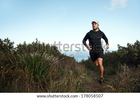 fitness running man on mountainn trail near ocean exercising for marathon training - stock photo