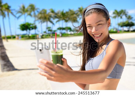 Fitness selfie woman drinking green vegetable smoothie taking self portrait photograph with smart phone after running exercise workout on beach. Healthy lifestyle with fit Asian Caucasian girl. - stock photo