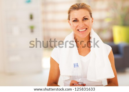 fitness senior woman with towel and water bottle - stock photo