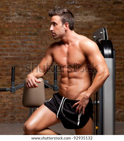 fitness shaped muscle man posing on dark gym - stock photo