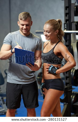 fitness, sport, exercising and diet concept - smiling young woman and personal trainer with clipboard writing exercise plan in gym - stock photo