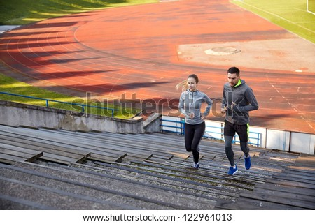 fitness, sport, exercising and lifestyle concept - happy couple running upstairs on stadium - stock photo