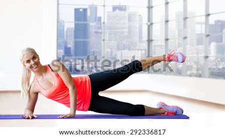 fitness, sport, exercising and people concept - smiling woman raising leg on mat over gym background - stock photo