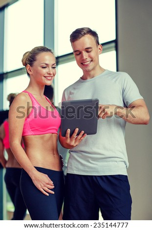 fitness, sport, exercising, technology and diet concept - smiling young woman and personal trainer with tablet pc computer in gym - stock photo
