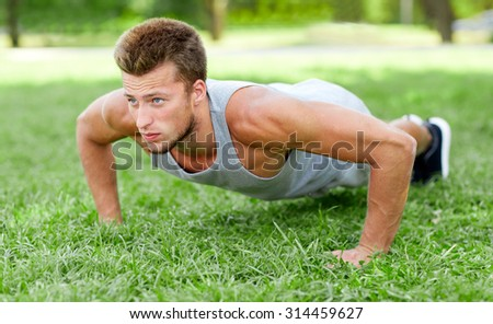 fitness, sport, exercising, training and lifestyle concept - young man doing push ups on grass in summer park - stock photo