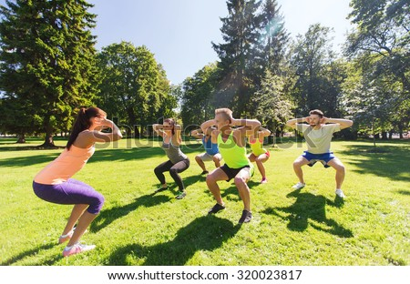 fitness, sport, friendship and healthy lifestyle concept - group of happy teenage friends exercising and doing squats at boot camp - stock photo