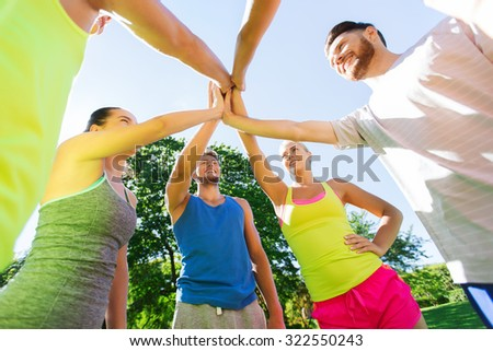 fitness, sport, friendship and healthy lifestyle concept - group of happy teenage friends or sportsmen making high five outdoors - stock photo